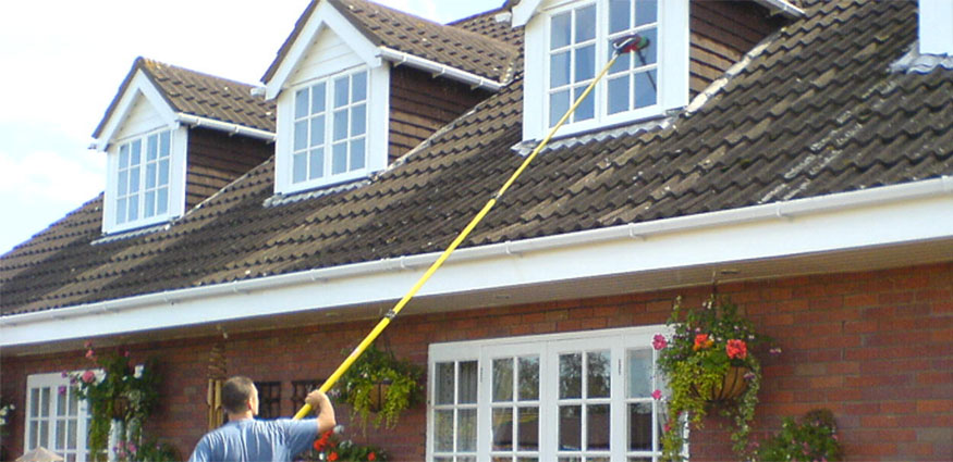 Photo of Steve Williams from All Around Property Cleaning Ltd cleaning an upstairs window using the water fed pole system.