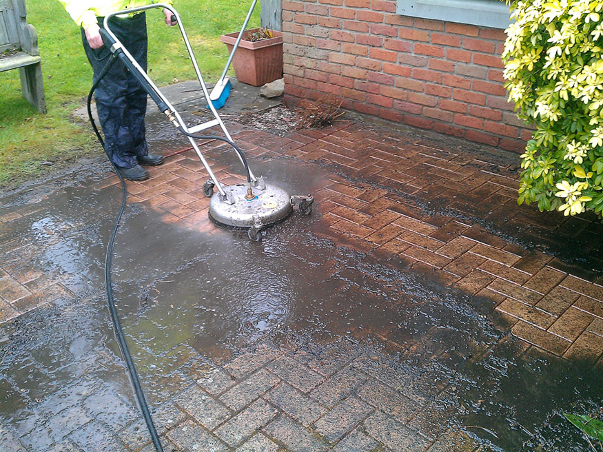 Photo of block paving being cleaned with a rotary cleaner.