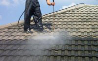 Photo of roof tiles being jet washed clean.
