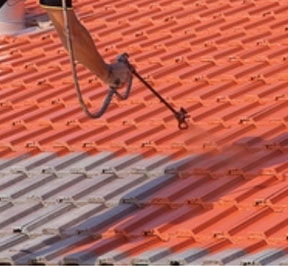 Photo of roof tiles being sprayed with a tinted coating.